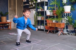 Image of young boy playing hopscotch