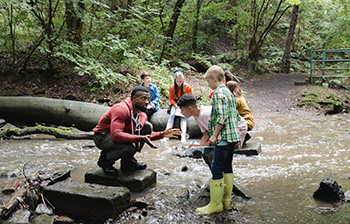 Image of teacher with young students exploring a creek
