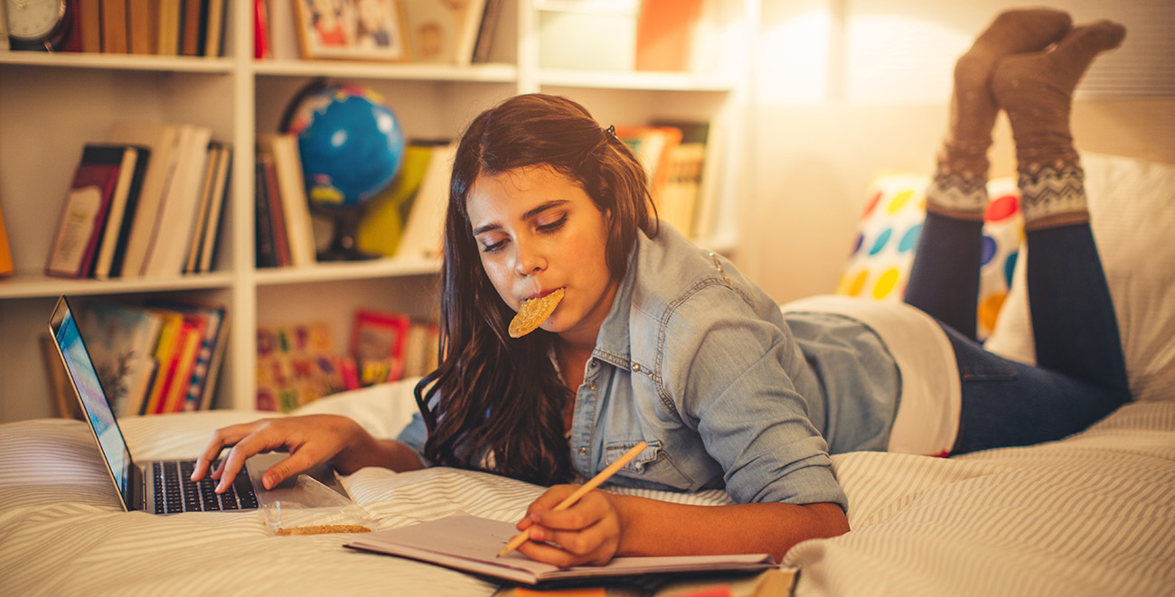 Image of teenager lying on bed eating a cookie and doing homework