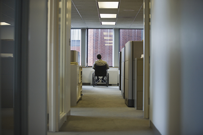 Man in a wheelchair looking out an office window