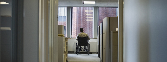 Worker in a wheelchair looks out the window