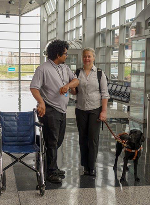 Image of a woman and her guide dog being assisted by an airport employee