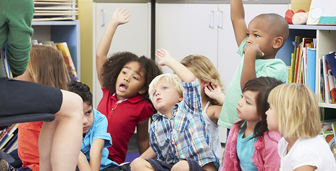 Young children raising hands at story time